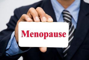 Businessman hand holding a menopause sign